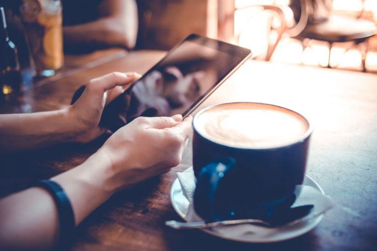 Donna che sorregge un tablet vicino a un cappuccino