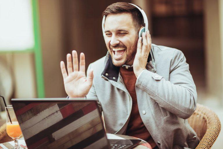 Uomo con cuffie wireless al PC