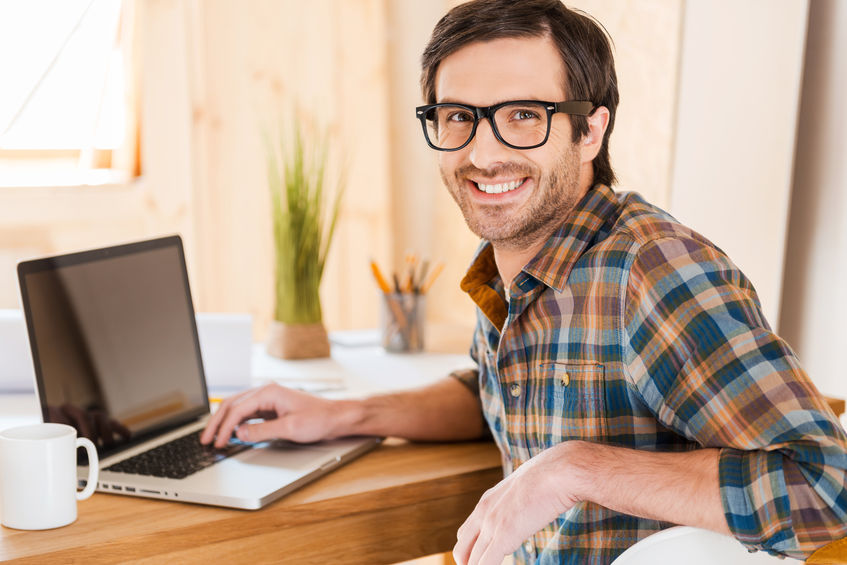 Great mood for working good. Handsome young man working on his laptop and looking at camera over shoulders while sitting at his working place