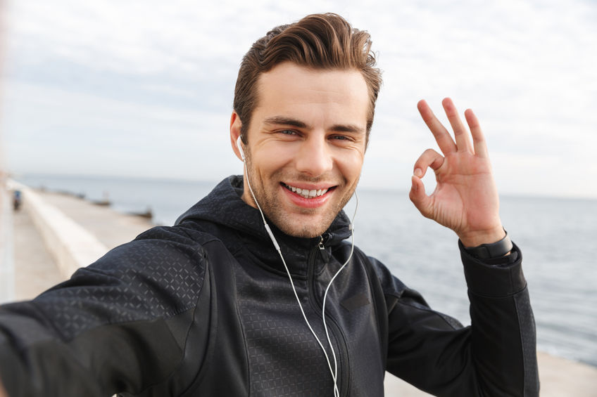 Image of satisfied sportsman 30s in black sportswear and earphon