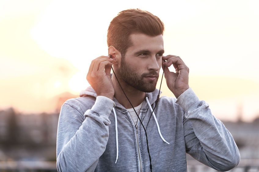 Music is always with me. Confident young man putting headphones into his ears and looking away while standing outdoors