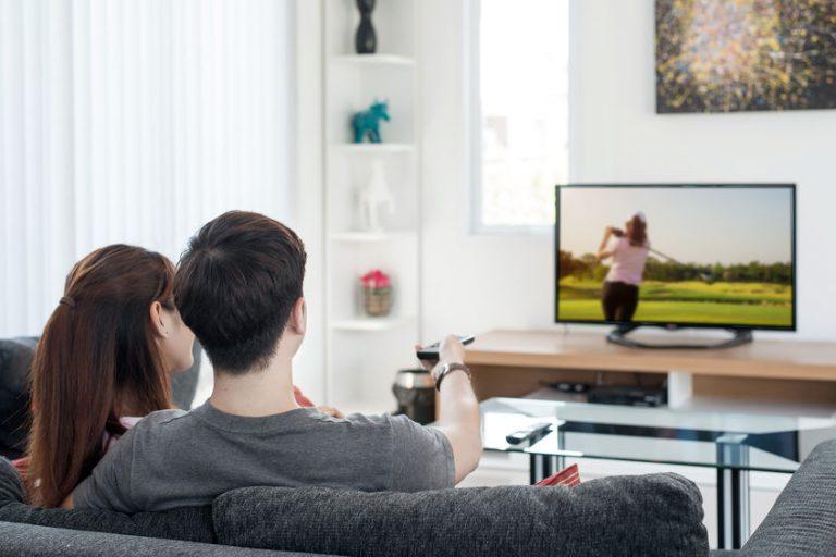 Coppia con telecomando guardando la TV