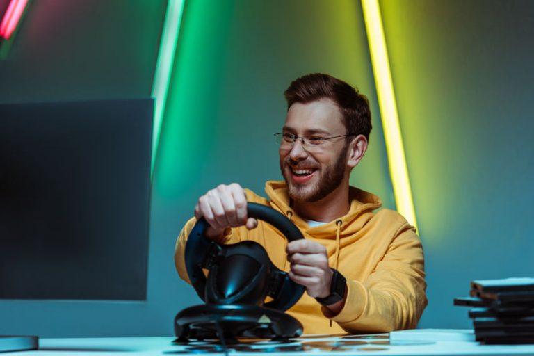 Gamer che si diverte giocando con un volante