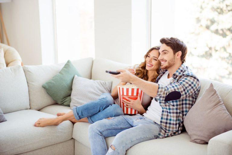 Coppia che guarda la TV mangiando popcorn