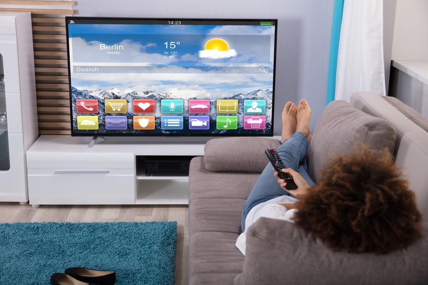 Donna che guarda la televisione con applicazioni colorate sullo schermo