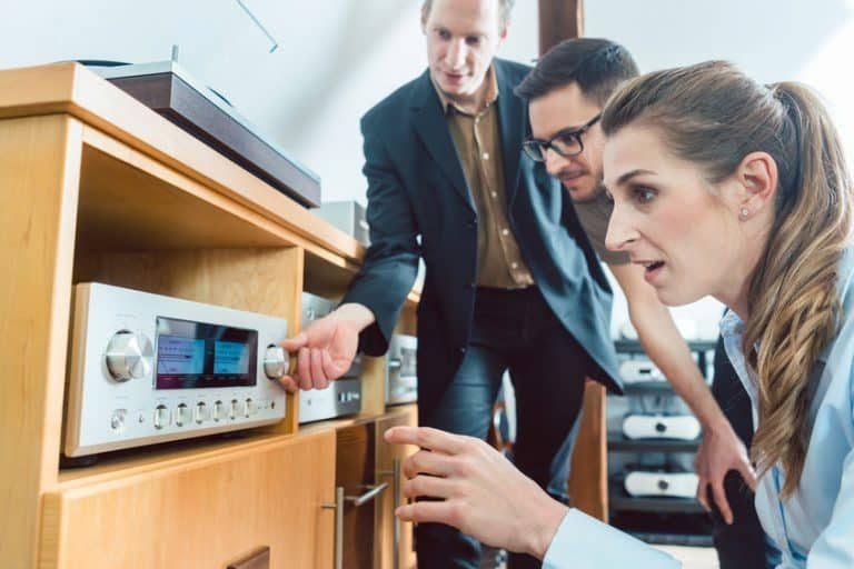 Tre persone che guardano un amplificatore Hi-Fi