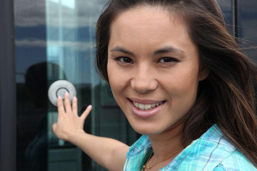 Donna che sorride suonando un campanello