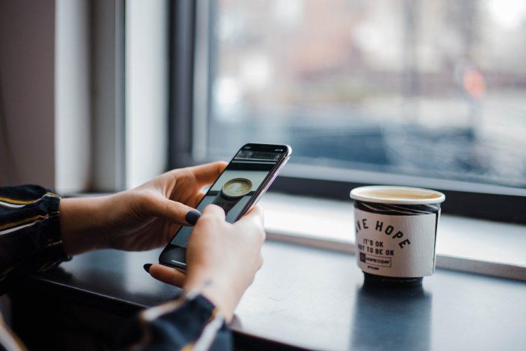 Donna che usa uno smartphone Huawei prendendo un caffè