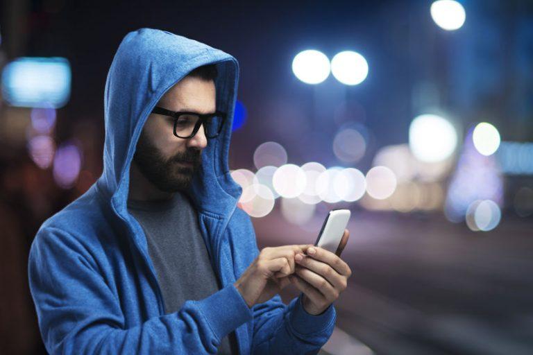 Uomo per strada con il telefono in mano