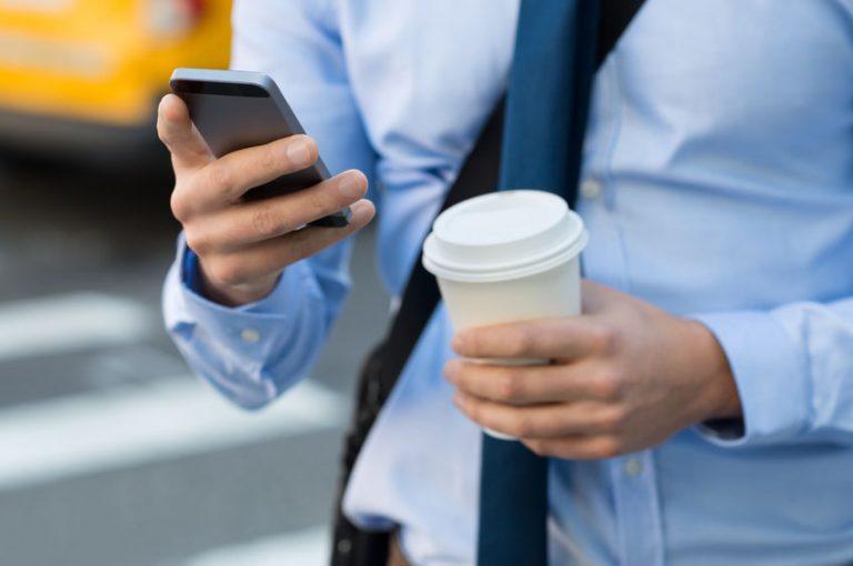 Uomo d'affari con smartphone Huawei in mano