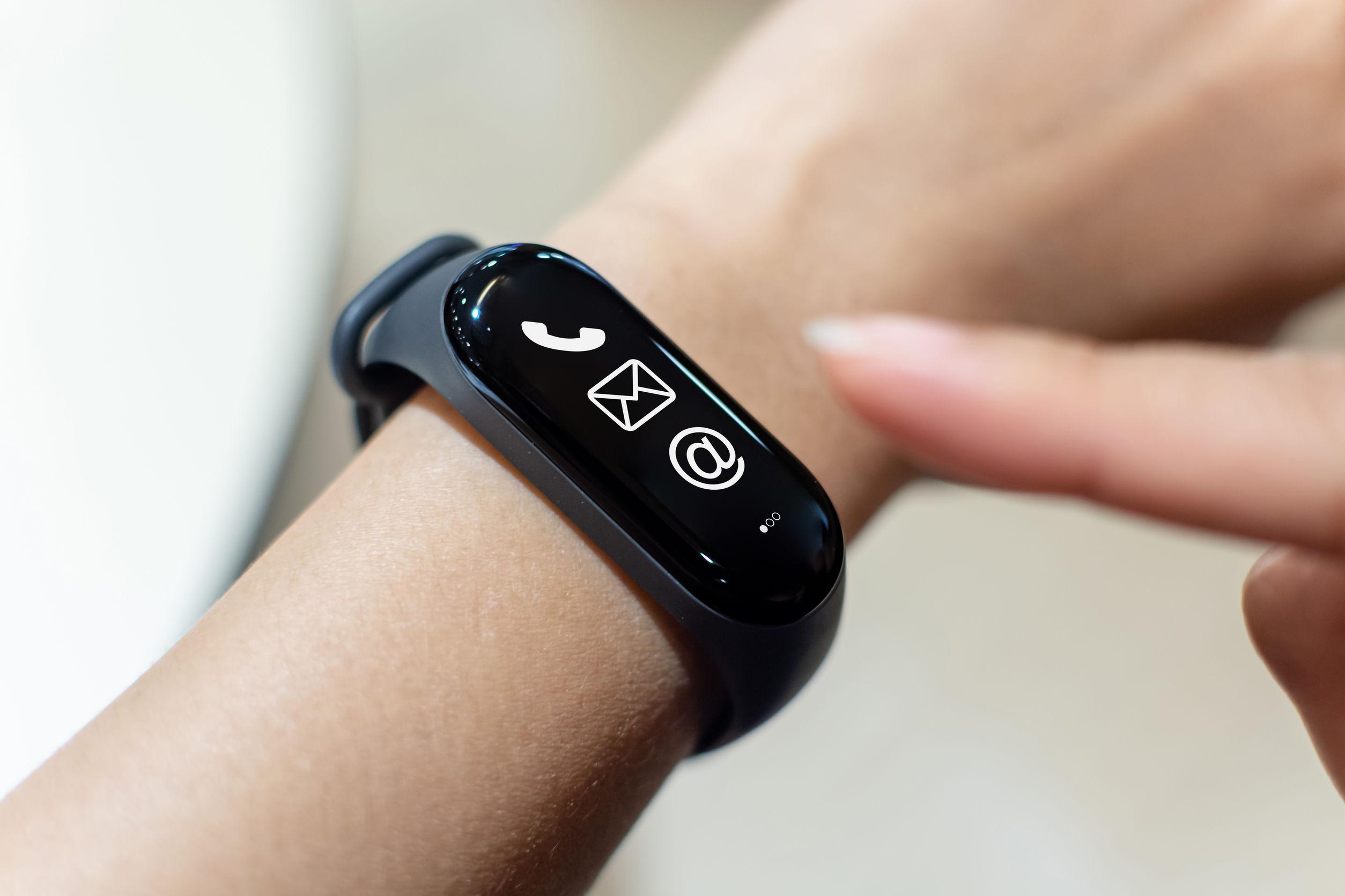 Mano de hombre usando un reloj inteligente con el icono de mensaje no leído en la pantalla