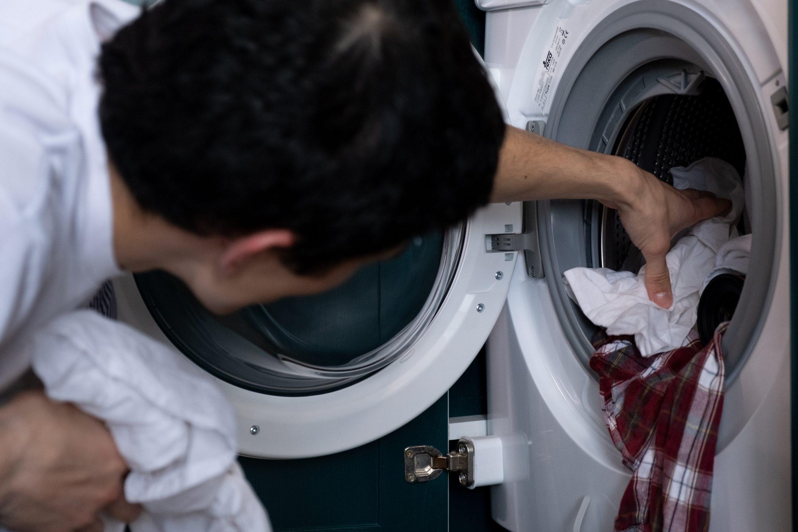 Hombre colocando ropa en lavadora