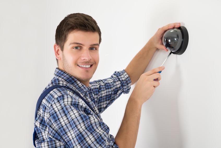 Técnico sonriendo instalando cámara de seguridad