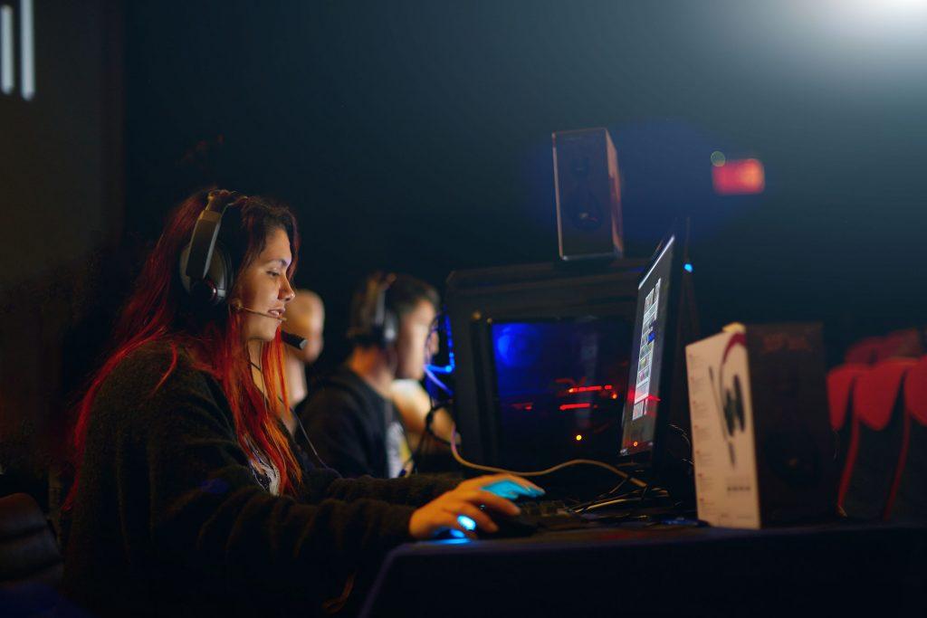 Chica gamer profesional juega en un videojuego de estrategia en su computadora.