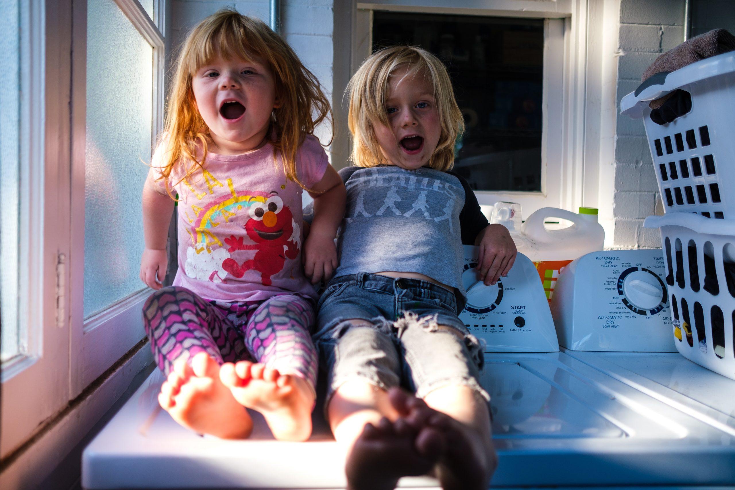 Dos niñas sentadas sobre una lavadora
