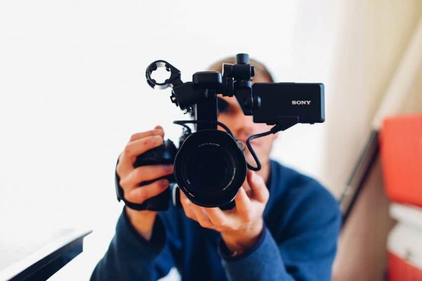 Imagem mostra um homem com uma câmera filmadora profissional Sony nas mãos.