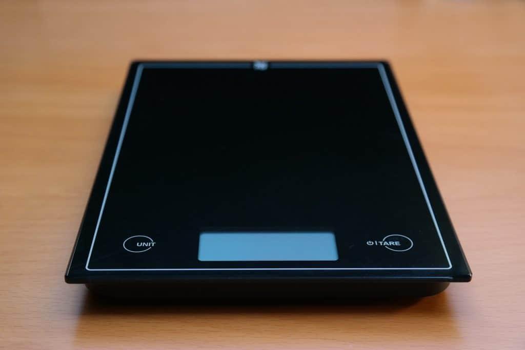 Na foto uma balança de precisão preta em cima de uma superfície de madeira.