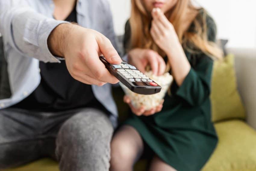 Imagem mostra duas pessoas em um sofá segurando um controle remoto e pipoca.