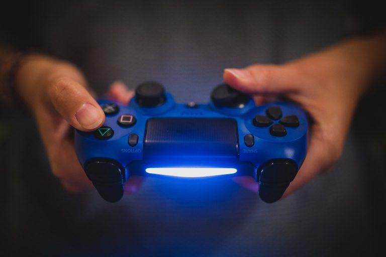 Imagem de pessoa jogando PS4 com controle azul e preto