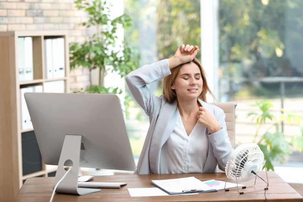 imagem mostra mulher sentada à mesa de trabalho se refrescando um ventilador usb