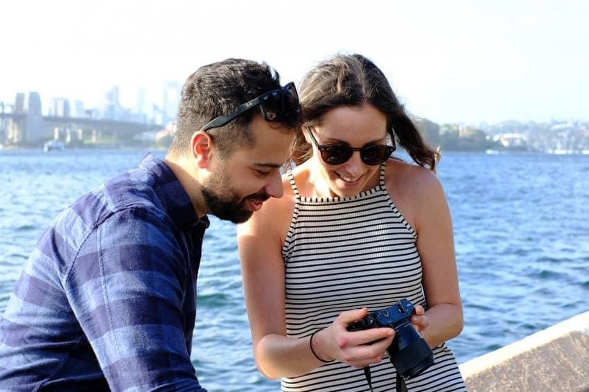 Homem e mulher vendo uma foto através do visor de uma câmera fotográfica.