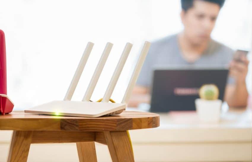 Modem em primeiro plano em cima de uma banqueta com uma pessoa ao fundo mexendo no notebook e celular.