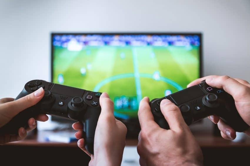 Imagem mostra dois controles de videogame em foco com uma TV ao fundo.