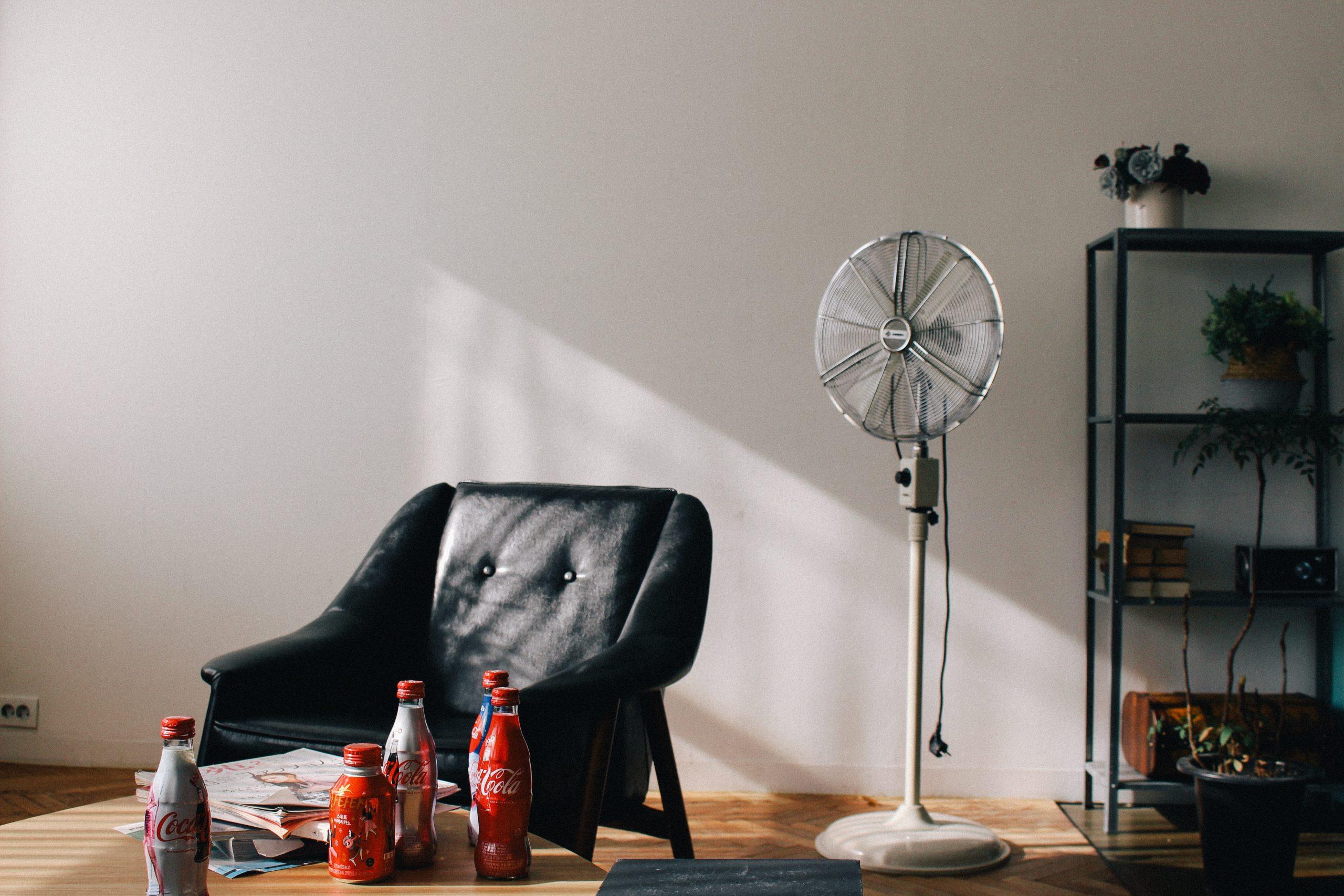 Na foto uma sala de estar com um sofá, uma mesa de centro e um ventilador de coluna.