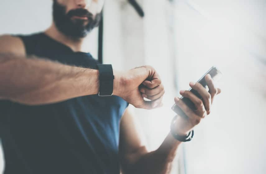 Imagem de homem em academia verificando informações em pulseira mi band.