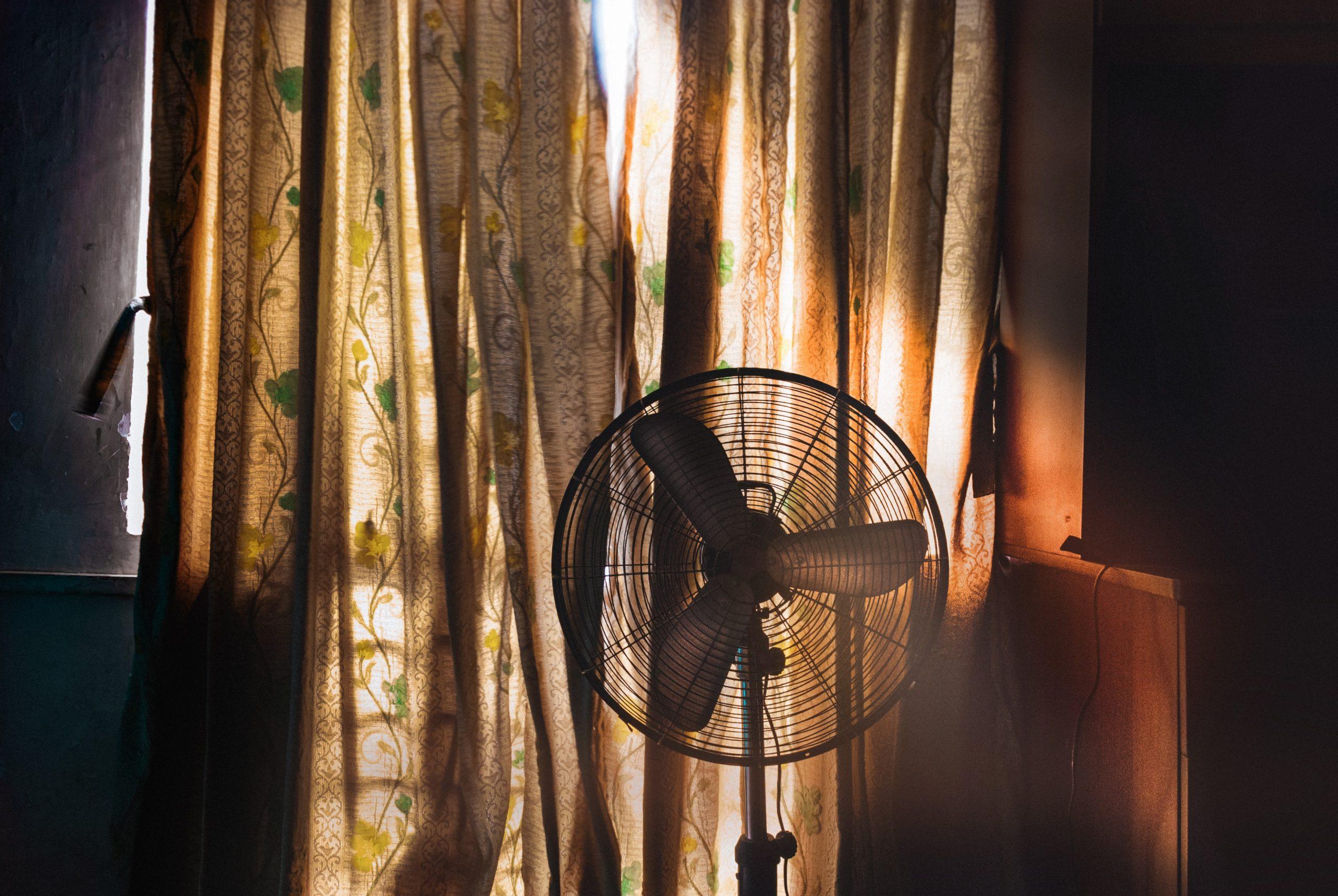Na foto uma ventilador de coluna em frente a uma cortina florida.