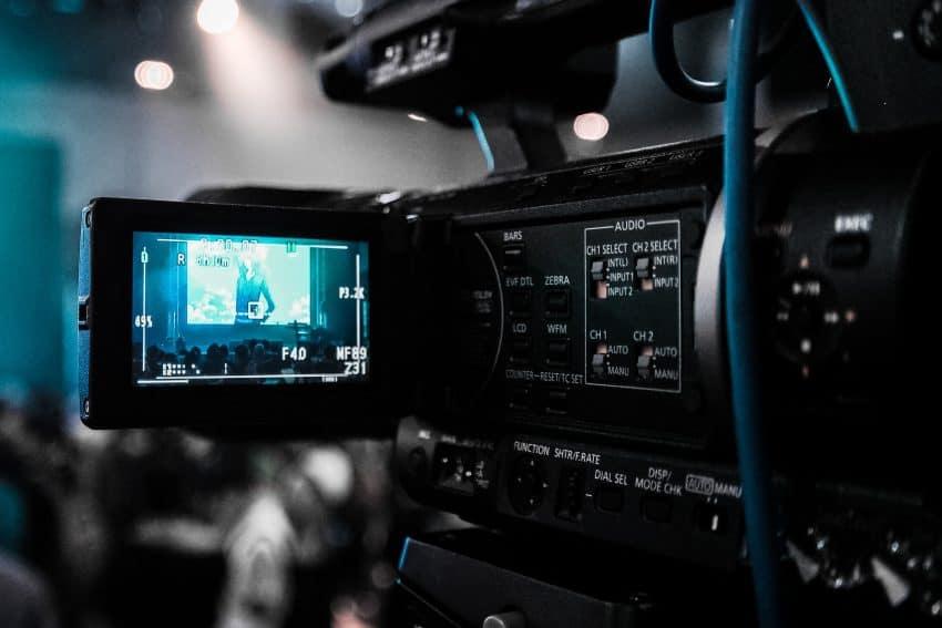 Imagem mostra uma câmera filmadora profissional durante as filmagens de um evento.