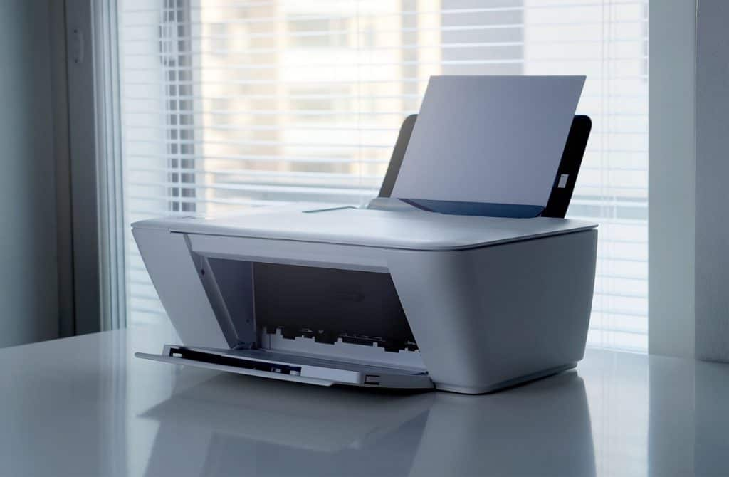 Imagem de impressora branca em cima de pesa com papéis.
