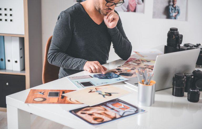 Imagem mostra um homem observando uma foto impressa.