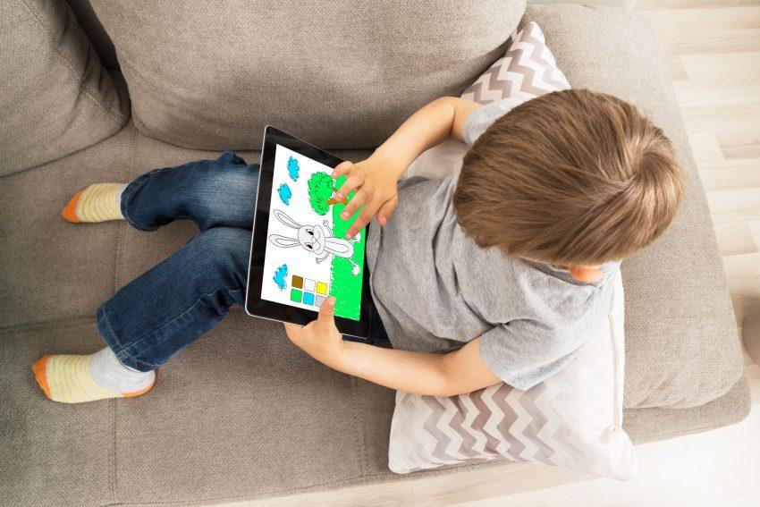 Menino sentado no sofá colorindo no tablet.