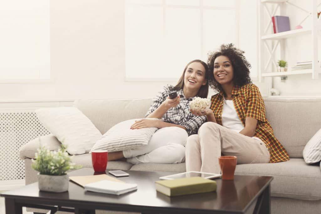 Na foto duas mulheres sentadas em um sofá dentro de uma sala de estar.