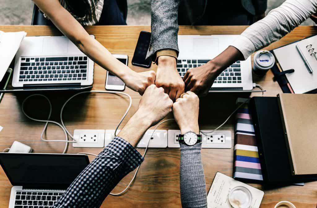 Imagem mostra uma mesa com computadores e cinco mãos se encontrando.
