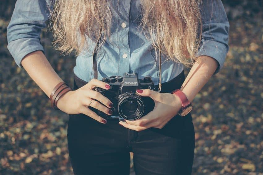 Imagem mostra uma pessoa segurando uma câmera fotográfica.