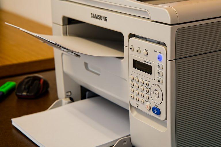 Imagem mostra uma impressora com diferentes tamanhos de papéis em suas gavetas.