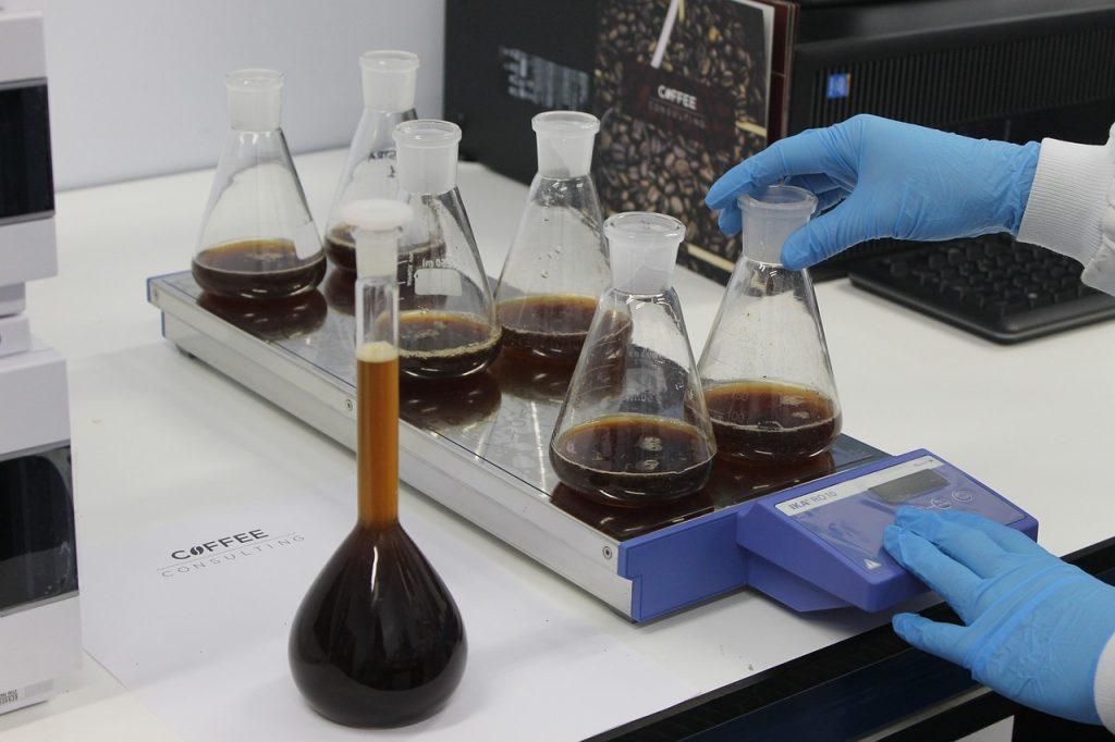 Na foto uma pessoa pesando seis recipientes com um líquido marrom em uma balança dentro de um laboratório usando luvas.