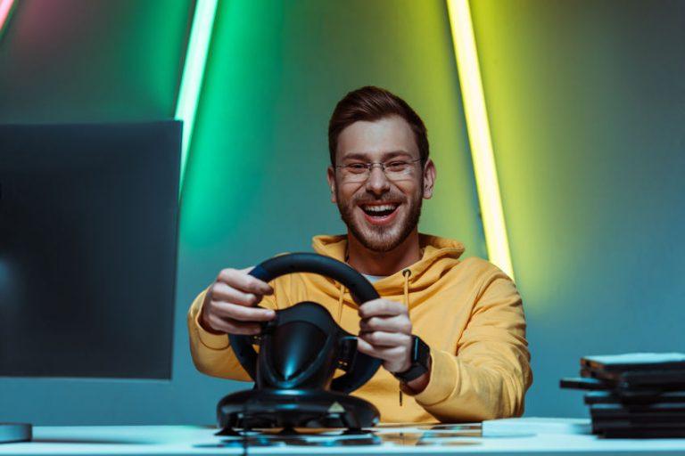 Imagem de homem jogando corrida com um volante para PS4