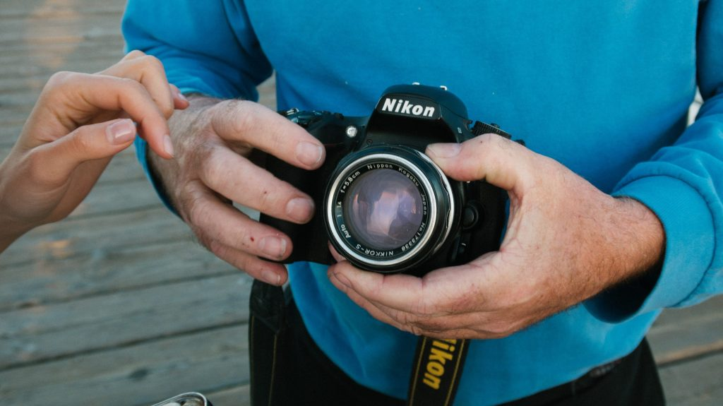 Imagem de um fotógrafo segurando a câmera Nikon.
