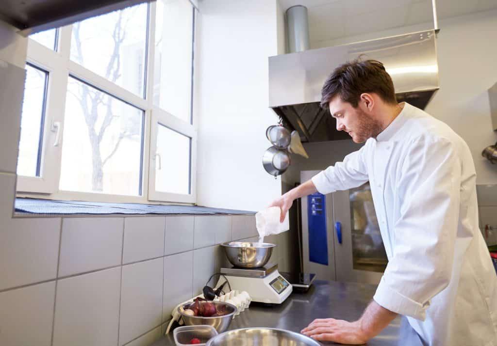 Na foto um homem de doma dentro de uma cozinha profissional medindo ingredientes em uma balança.