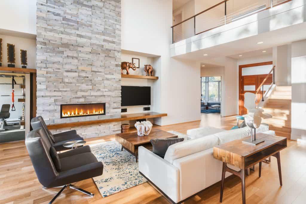 Na foto uma sala de estar com uma lareira, um televisor, sofás e poltronas.
