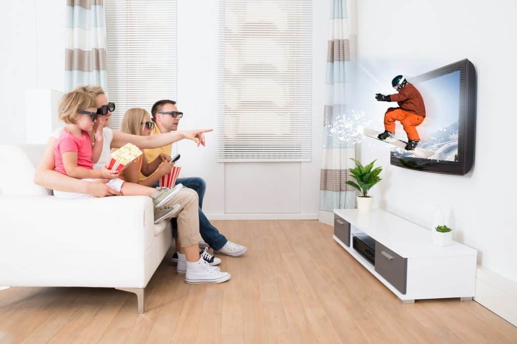 Em um sofá uma família com quatro pessoas usando óculos 3D assistem um programa de esportes na neve.