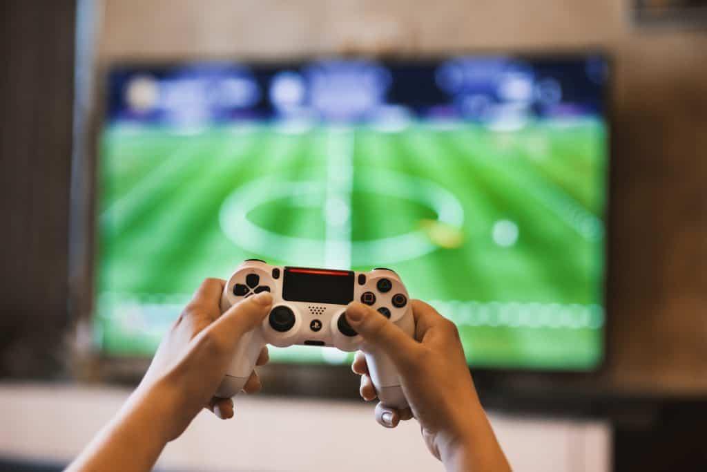 As mãos de uma pessoa em um joystick jogando um jogo de videogame.