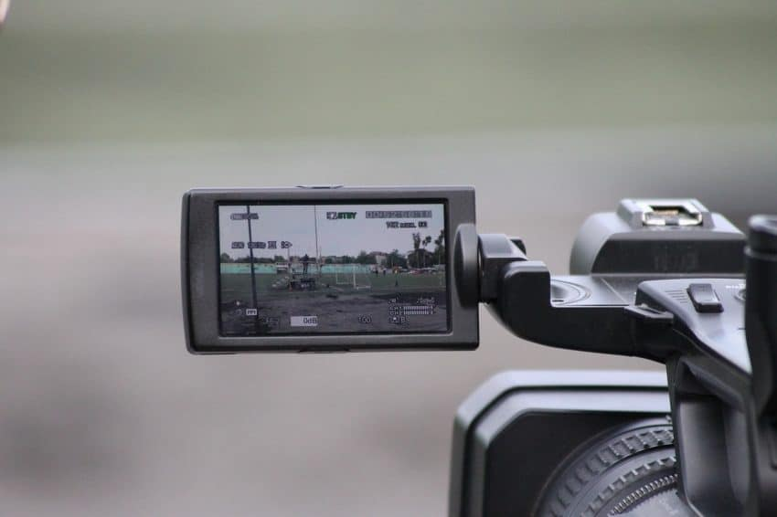 Imagem mostra o visor de uma filmadora fazendo a filmagem de um praça.