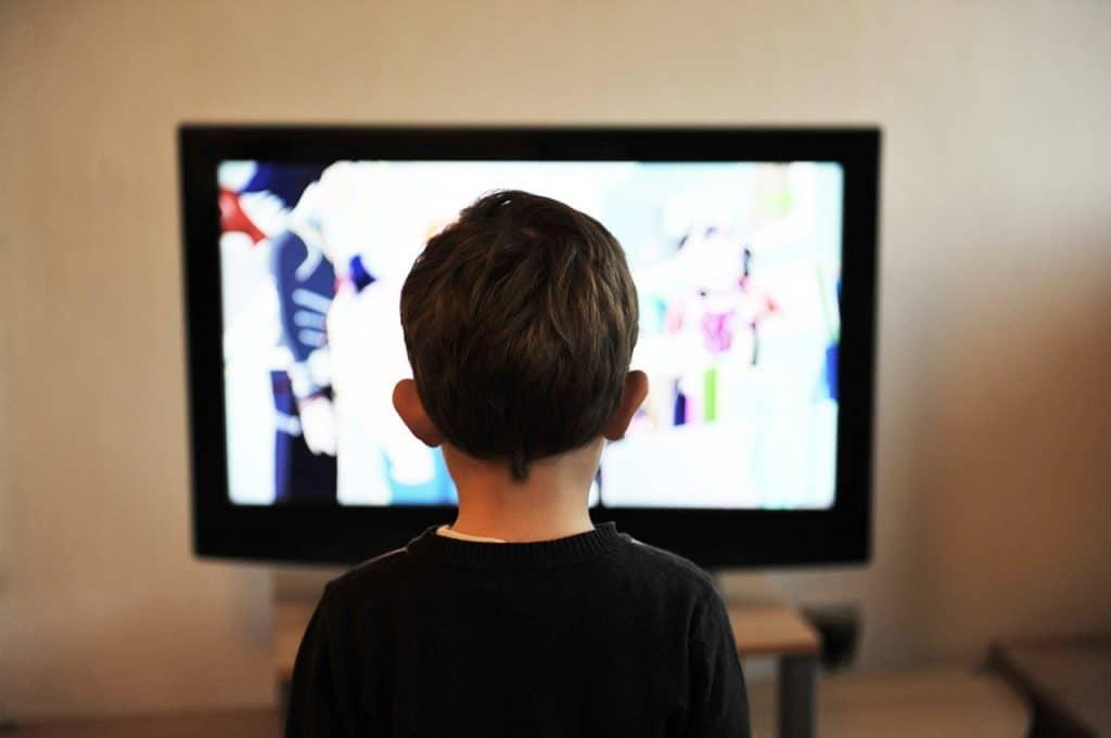 Imagem de criança assistindo TV.