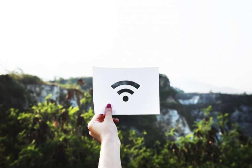 Mulher segura placa com símbolo do wi-fi.