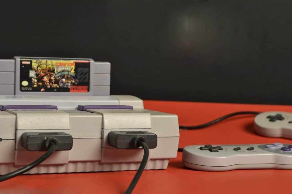 Foto de console de super nintendo com jogo e controle ao lado.