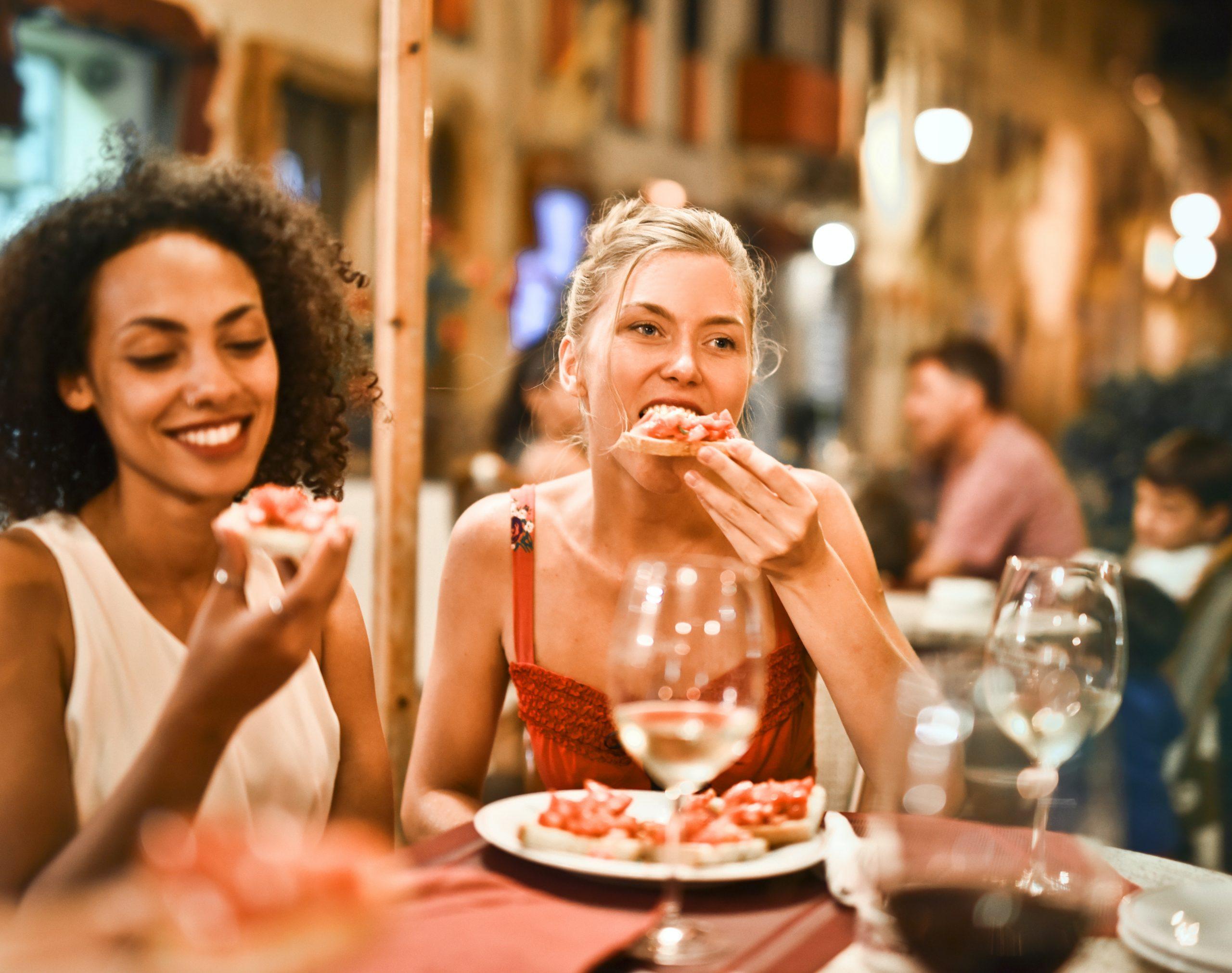 Na foto duas mulheres comendo em um restaurante.